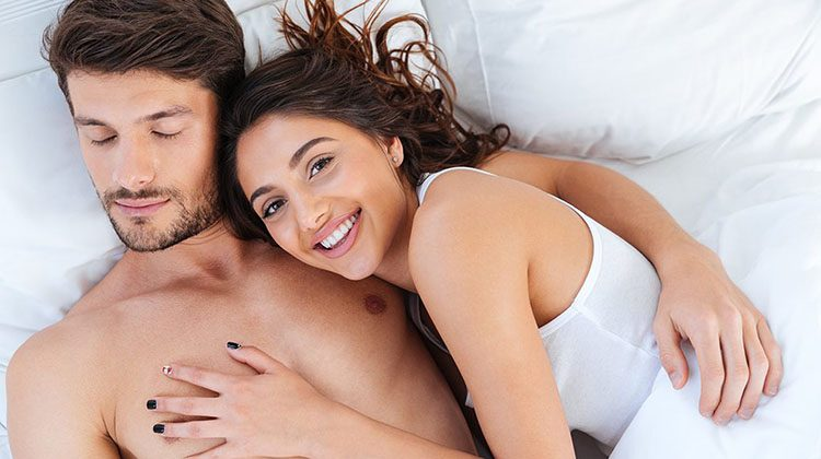 Close-up portrait of a happy couple sleeping and hugging in bed at home